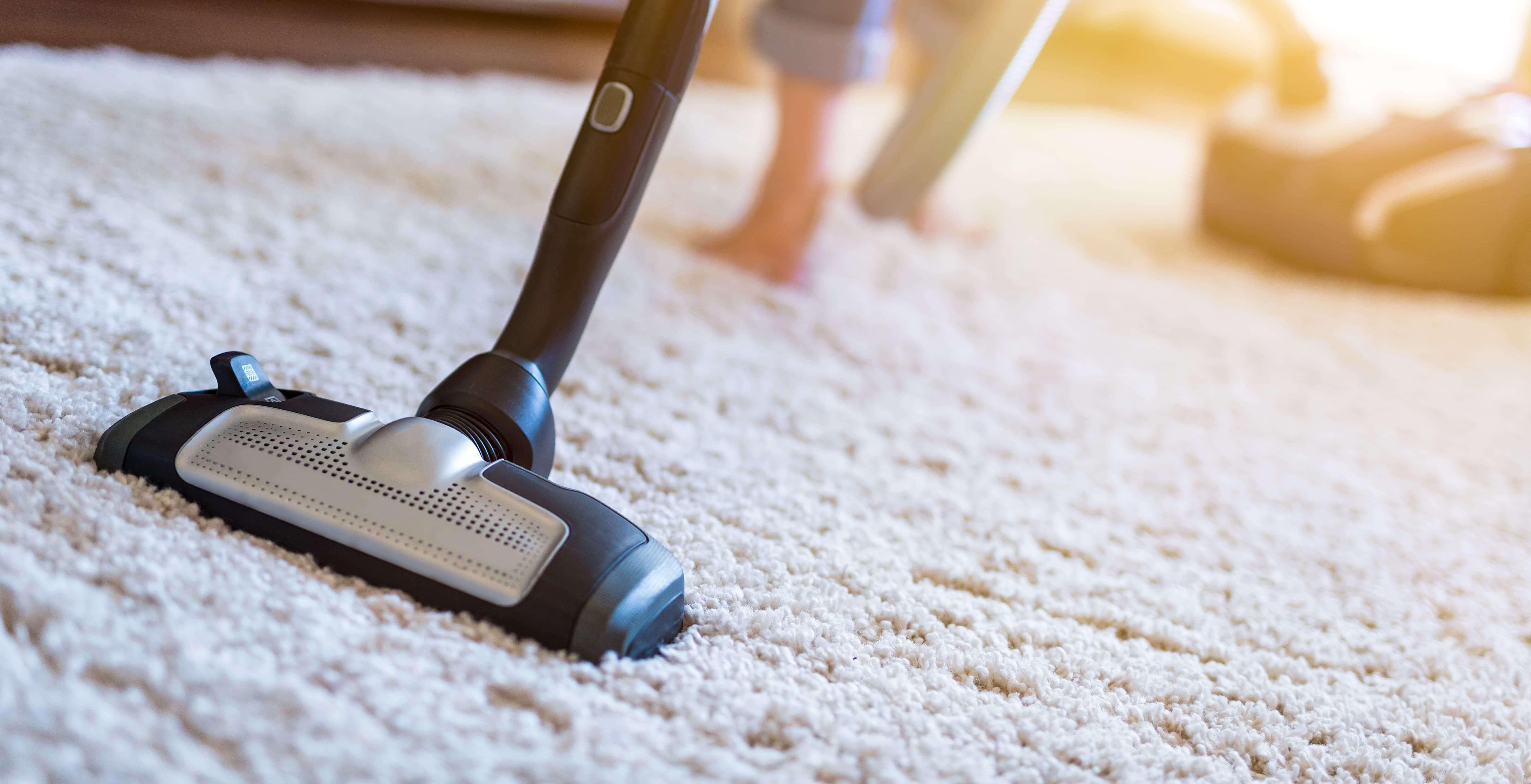 Person saugt Teppichboden als Tipp für Reinigung von Bodenbelägen von Ambiente Ackermann